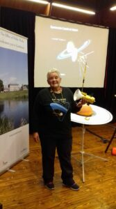 Deirdre Kelleghan holding her model of Cassini . In the background is her model of the planet Saturn . The venue is Castletown House and Parklands in Ireland . The event was Spectacular Cassini at Saturn a new drawing workshop by Deirdre