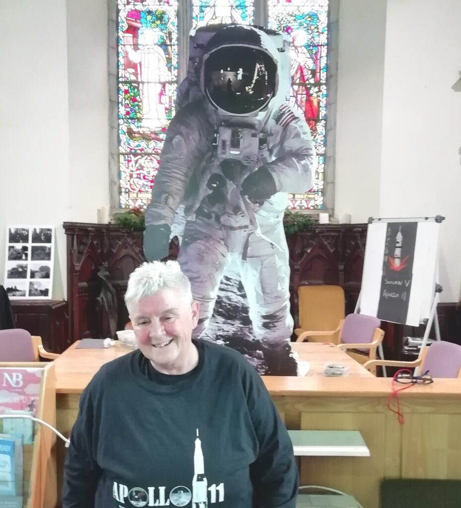 A cardboard Buzz Aldrin looking great infront of a massive stained glass window in Ballinrobe Library