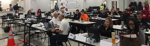 """The Kentucky Division of Emergency Management (KYEM) set up a Regional Response Coordination Center (RRCC) in Hopkinsville. Shown is the RRCC just before the 9am briefing on """"game day"""". One of the lighter moments came when the chief 911 operator reported emergency calls were down from the previous year, but they were getting requests for help with WiFi."""
