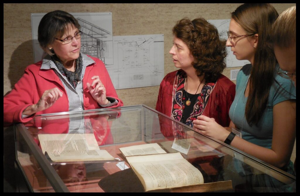 Prof. Buie discussing Copernicus with KAS attendees.  Inside the case, to the left, is an original copy of Copernicus's De Revolutionibus.  In the foreground is an original copy of Isaac Newton's Principia, with notes written in it by Newton himself.  See below.