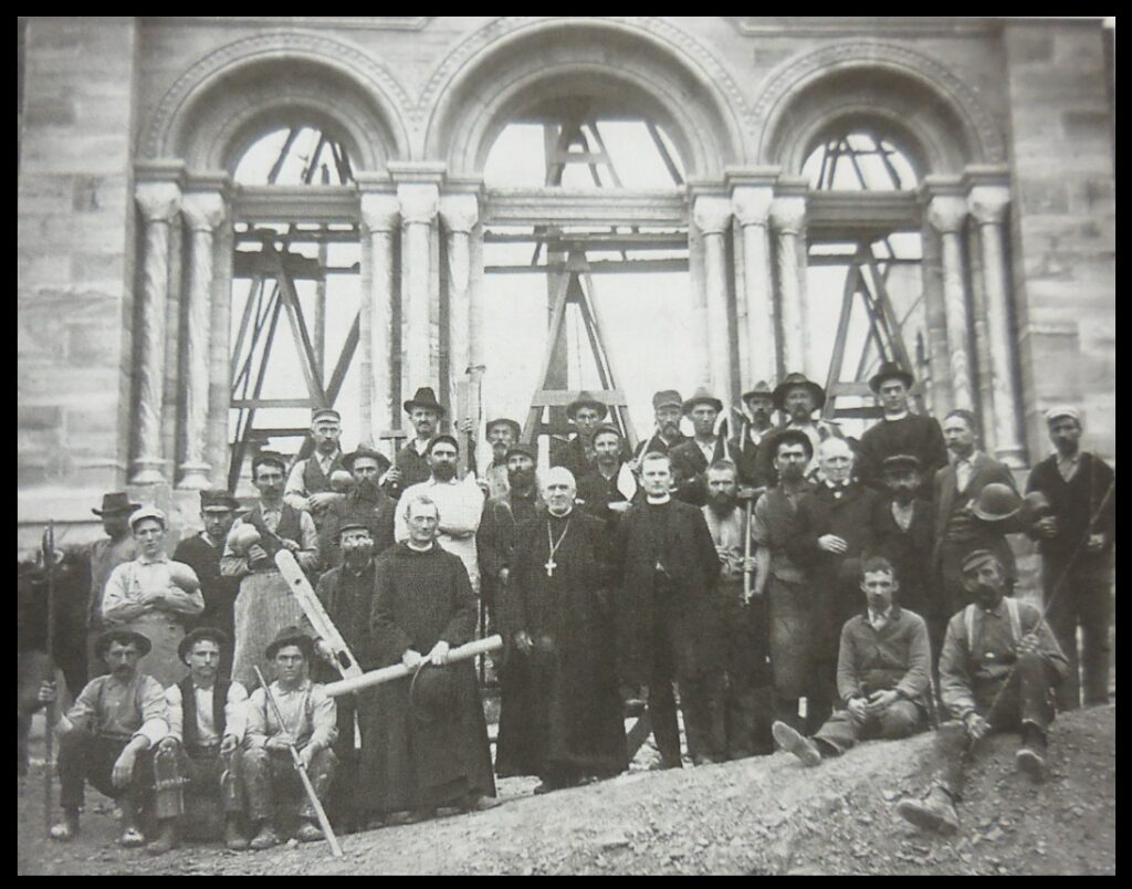 """Photo from the 2004 book To Prefer Nothing to Christ: St. Meinrad Archabbey 1854-2004, showing """"construction workers for the Abbey Church, 1900-1904"""". While most histories do not provide much information about people such as stonemasons, To Prefer Nothing to Christ does contain some information about those who built the abbey, in its chapter on the construction of the abbey church. For example, it mentions """"the head oxen driver, John Tuchscherer, who by the mere roar of his mighty voice and a crack of the whip was able to persuade his two, sometimes, three, and even four yoke of oxen to move the heaviest stone over the muddiest roads (if roads they should be called) and up the steep hill to the building site [p. 458]."""" Clearly John Tuchscherer had, in his own way, studied and tested nature to see how things work, and to determine what was true."""