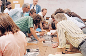 Members of the Voyager science team pore over fresh images of Neptune's moon Triton as data from Voyager 2 stream into JPL in August 1989. Photo by: D. Patterson and B. Rowe. Courtesy NASA/JPL-Caltech.
