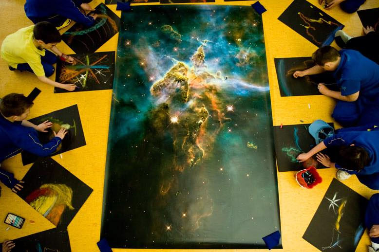 The Hubble 20th anniversary print of the Carina Nebula. The image is surrounded by children from St Peters NS in Dublin. They are drawing sections of it as drawing the entire 8 X 5 print was very difficult. The children had never seen anything like it in their lives before.