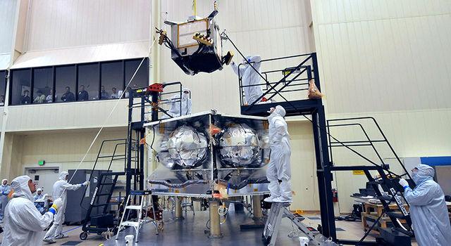 Technicians install a special radiation vault onto the propulsion module of NASA's Juno spacecraft at the Lockheed Martin facility in Denver, Colorado.