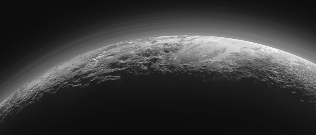 Pluto's Majestic Mountains, Frozen Plains and Foggy Hazes: Just 15 minutes after its closest approach to Pluto on July 14, 2015, NASA's New Horizons spacecraft looked back toward the sun and captured this near-sunset view of the rugged, icy mountains and flat ice plains extending to Pluto's horizon. The smooth expanse of the informally named icy plain Sputnik Planum (right) is flanked to the west (left) by rugged mountains up to 11,000 feet (3,500 meters) high, including the informally named Norgay Montes in the foreground and Hillary Montes on the skyline. To the right, east of Sputnik, rougher terrain is cut by apparent glaciers. The backlighting highlights over a dozen layers of haze in Pluto's tenuous but distended atmosphere. The image was taken from a distance of 11,000 miles (18,000 kilometers) to Pluto; the scene is 780 miles (1,250 kilometers) wide. Credits: NASA/JHUAPL/SwRI