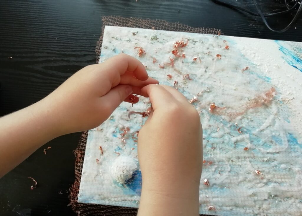Cal helps sprinkle the copper shavings all over the canvas. They represent the dunes on Mars as imaged by NASA Odyssey spacecraft